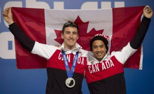 Canadian speed skaters Denny Morrison and Gilmore Junio hold up a Canadian flag  at the Sochi Winter Olympics on February 16, 2014. (Photo credit: THE CANADIAN PRESS/Adrian Wyld)