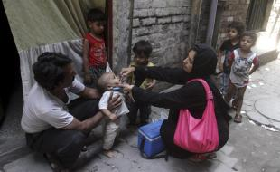 A Pakistani health worker gives a polio vaccine to a child in Lahore, Pakistan on May 20, 2014. (AP Photo/K.M. Chaudary).