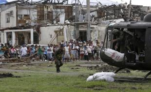 Typhoon survivors watch as a Philippine Air Force helicopter unloads sacks of relief supplies at Tanauan township, Leyte province in central Philippines Friday Nov. 22, 2013. (AP Photo/Bullit Marquez)