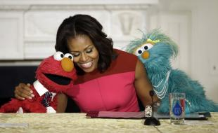 First Lady Michelle Obama, center, with Elmo, left, and Rosita, right, as they help promote eating fresh fruit and vegetables to kids on October 30, 2013. (AP Photo/Pablo Martinez Monsivais)