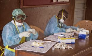 Health workers wearing clothing and equipment to protect against Ebola sit at a desk at the Kenema Government Hospital in Sierra Leone in August, 2014. (AP Photo/ Michael Duff)