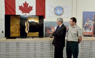 Prime Minister Stephen Harper applauds the find from the Victoria Strait Expedition of Sir John Franklin's doomed 1845 Arctic expedition as Parks Canada's Ryan Harris looks on in Ottawa on September 9, 2014. (THE CANADIAN PRESS/Sean Kilpatrick)