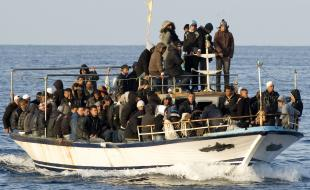 FILE -- In this 2011 photo, a boat loaded with migrants is spotted at sea off Lampedusa, Italy. (AP Photo/Antonello Nusca, File)
