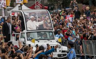 Pope Francis waves to the crowd from his Pope-Mobile while on his way to lead Mass at Benjamin Franklin Parkway in Philadelphia, USA, on September 27, 2015. (Photo courtesy EPA/ANDREW BURTON / POOL.)